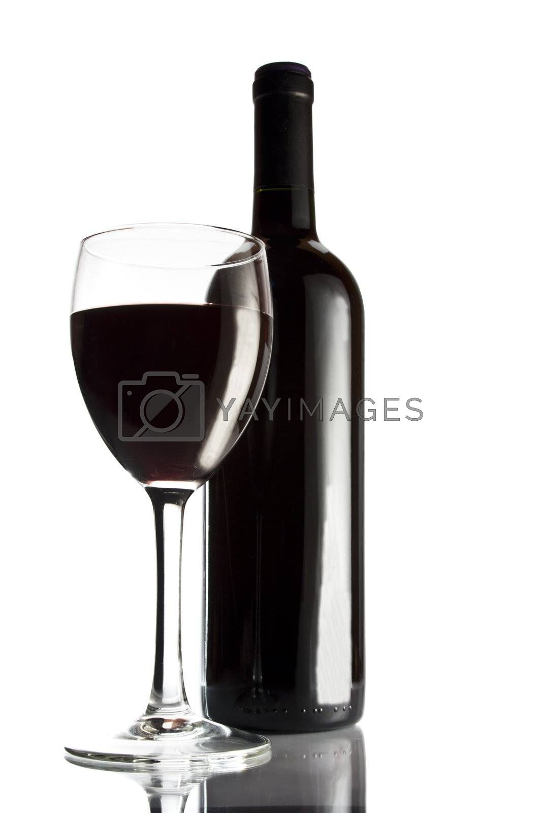 Bottle of red wine and glass. Studio shot.