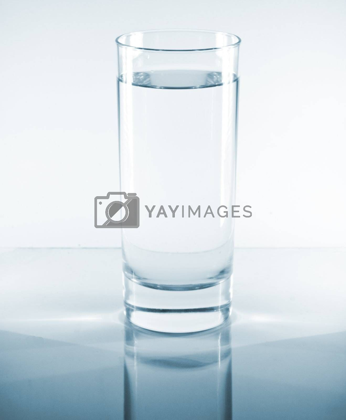 Glass of water on a reflective table top