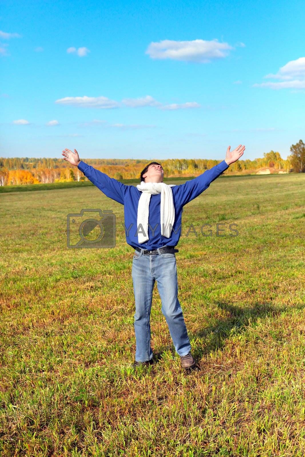 man on autumn field rising up his hands