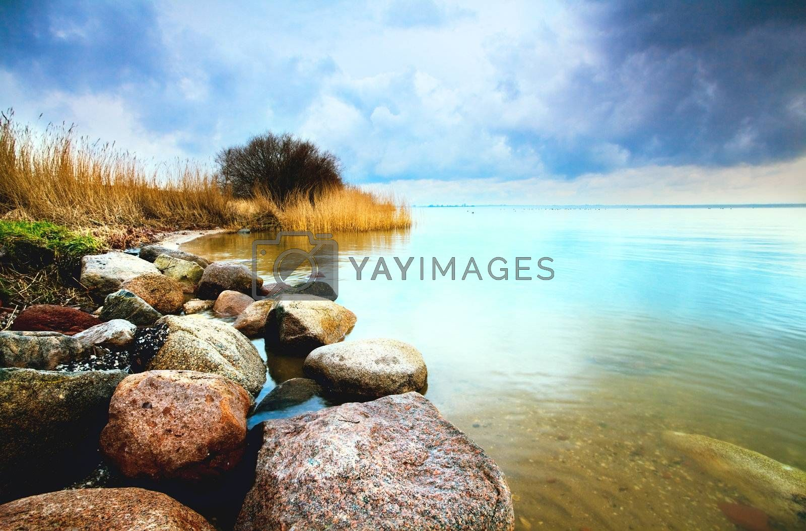 colorful view on the big lake with stones and clouds on sky