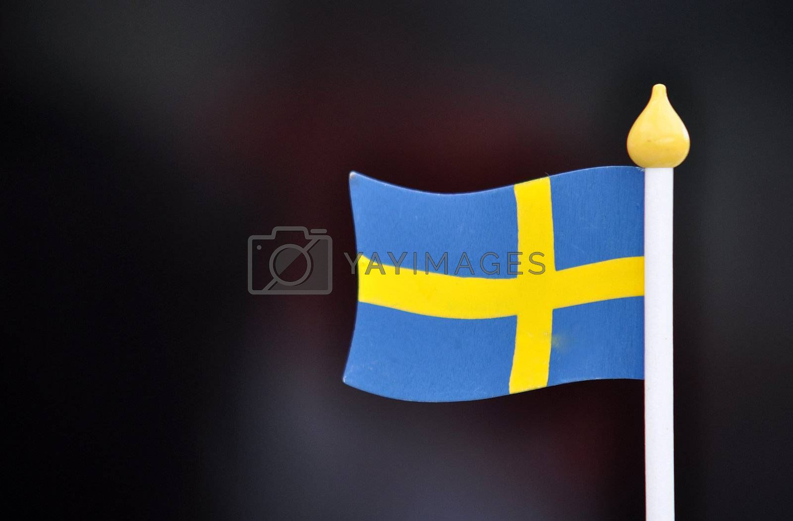 A swedish small wooden flag against a out-of-focus background.