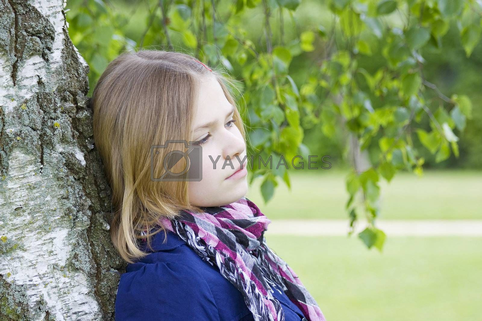 Portrait of young girl standing near birch tree in summer green park
