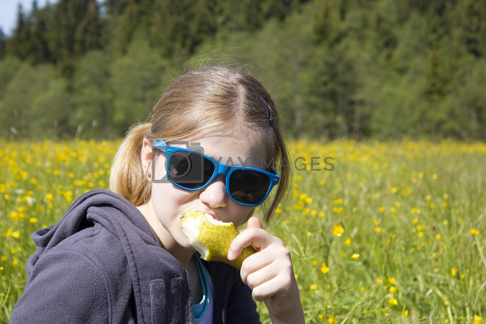 Young girl with fresh yellow pear