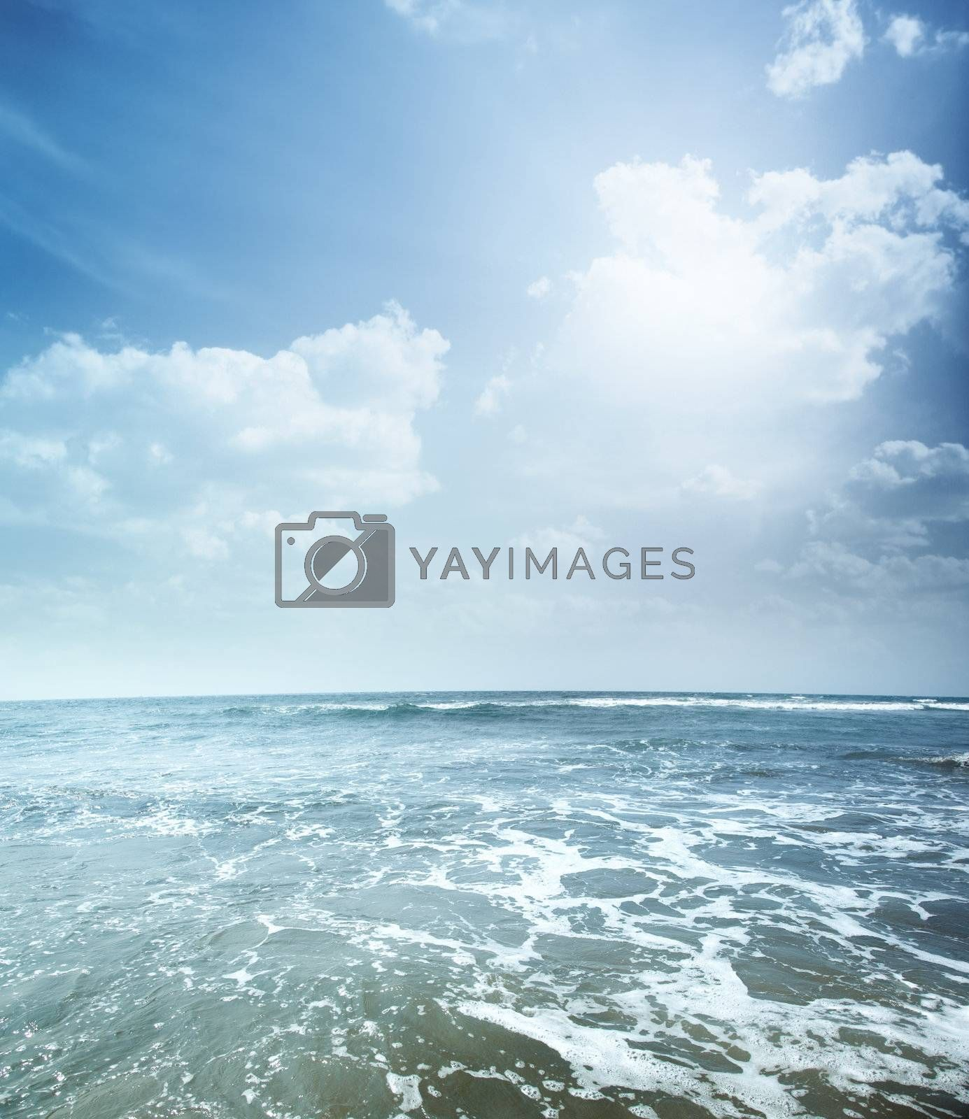 Vertical photo of the blue sea with foam and cloudy sky. Vibrant colors
