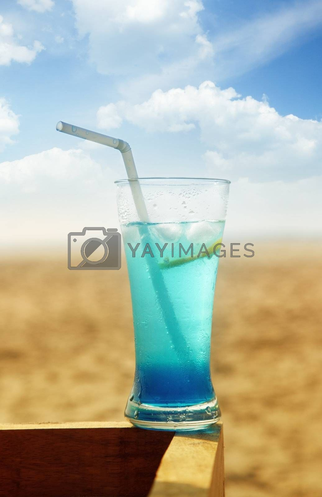 Close-up photo of the glass with fresh cold cocktail at the summer beach. Vibrant colors