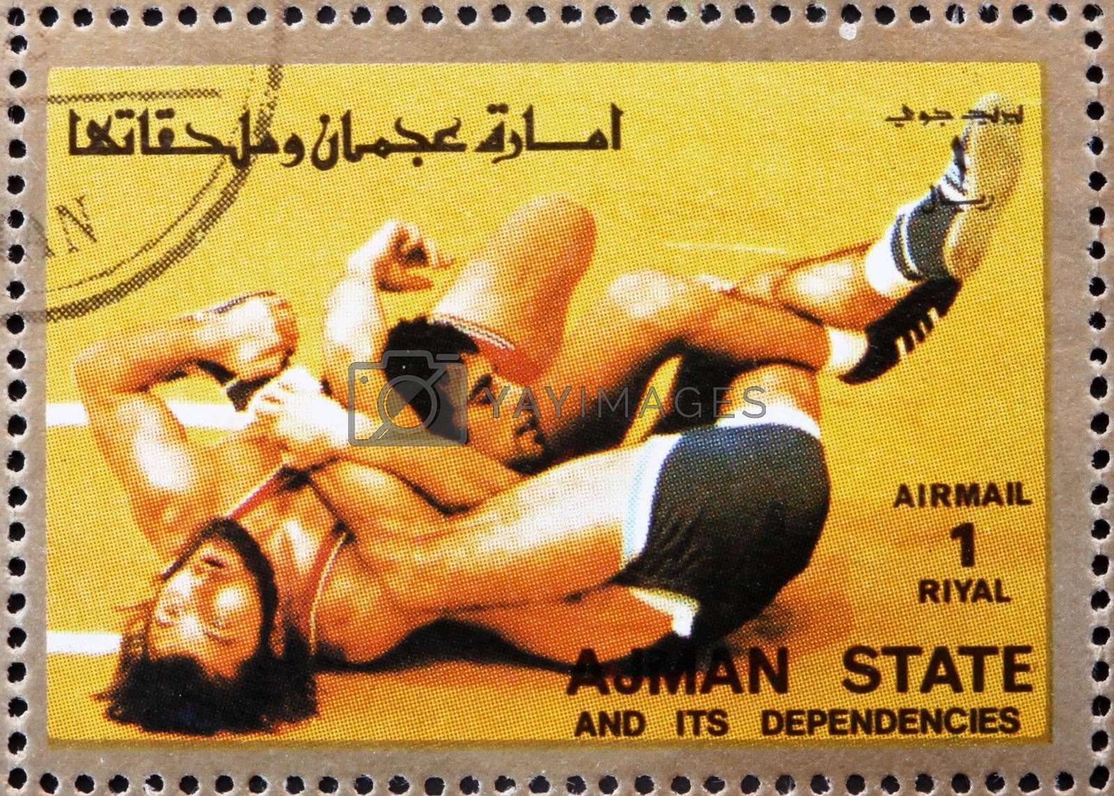 AJMAN - CIRCA 1973: a stamp printed in the Ajman shows Wrestling, Olympic sports, circa 1973