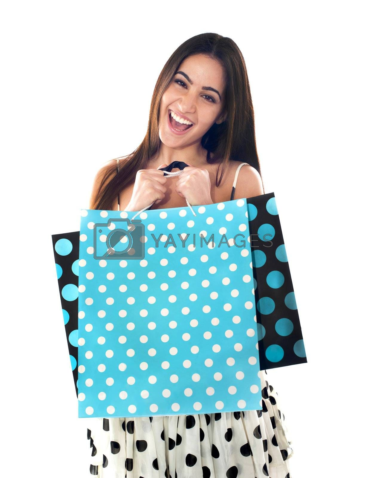 Excited young shopaholic woman holding shopping bags. All on white background