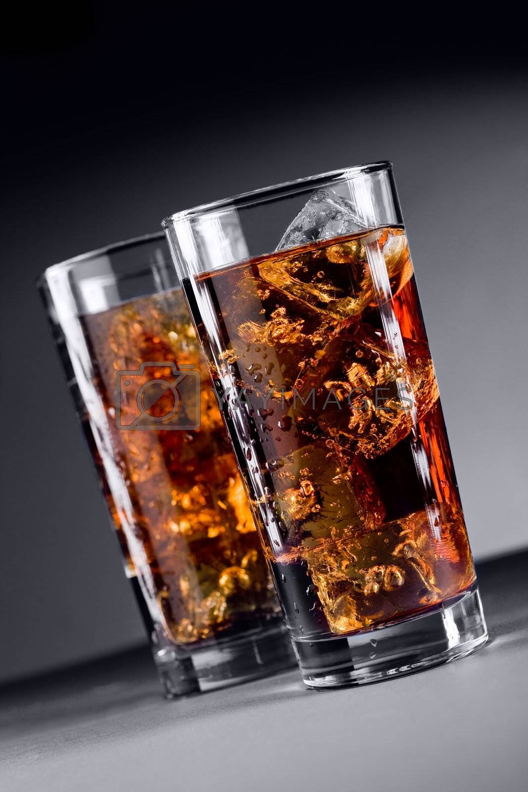 Photo of delicious cold glass with cola and ice cubes