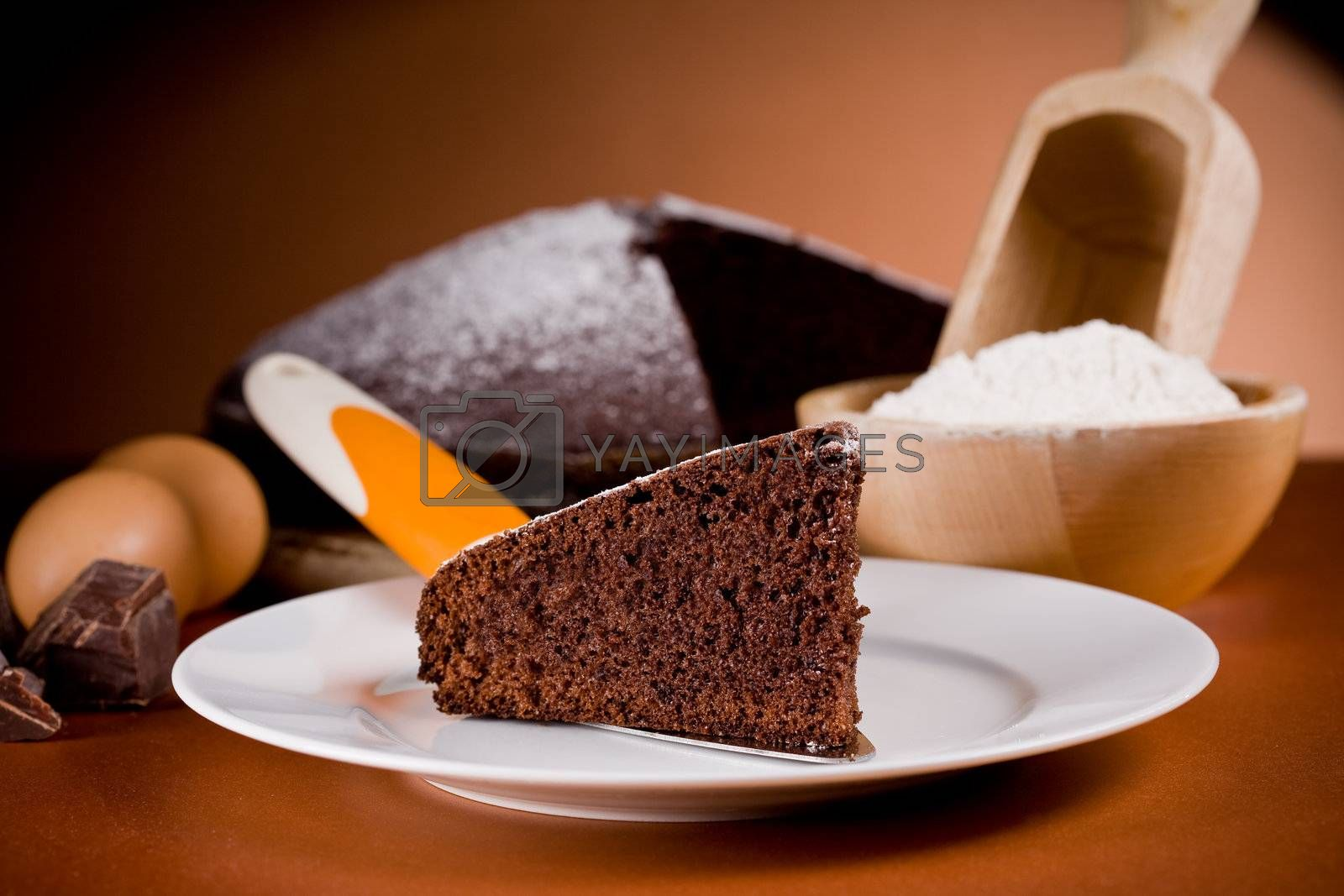 photo  of delicious chocolate cake with ingredients on brown background