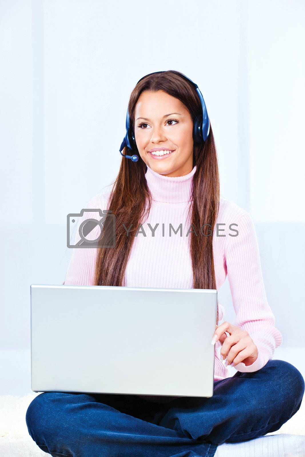 Pretty young woman with headphones and  laptop at home