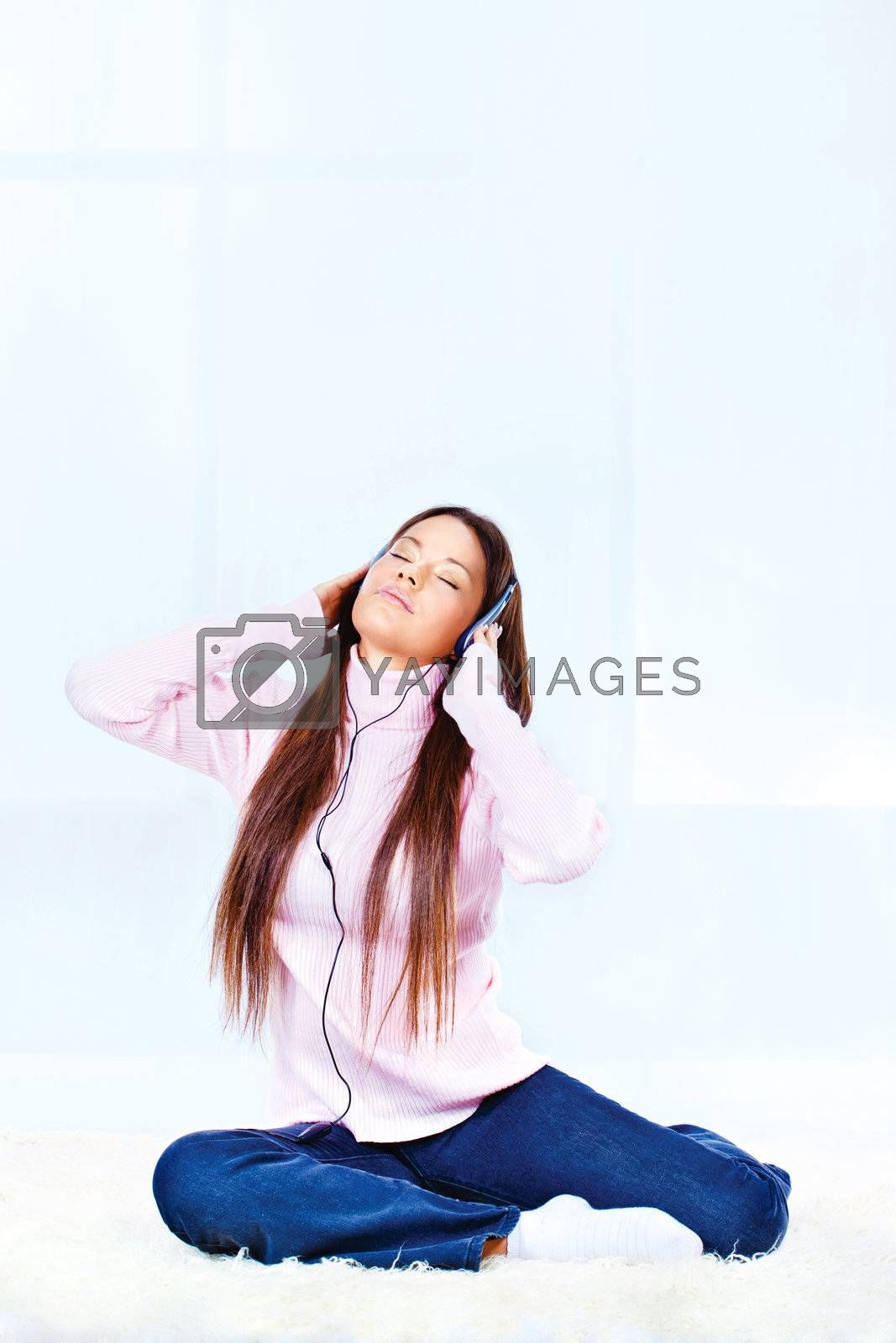 Pretty young woman with headphones listening music at home