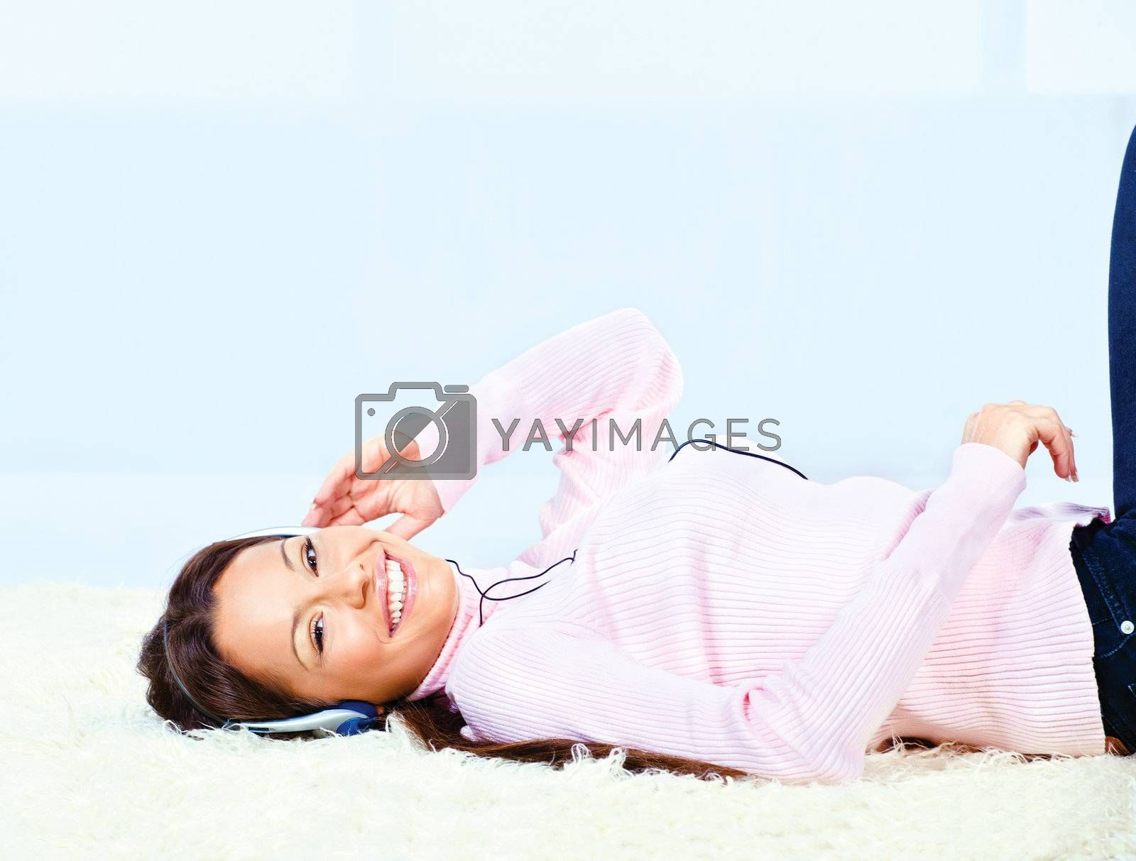 Pretty young woman on carpet with headphones listening music at home