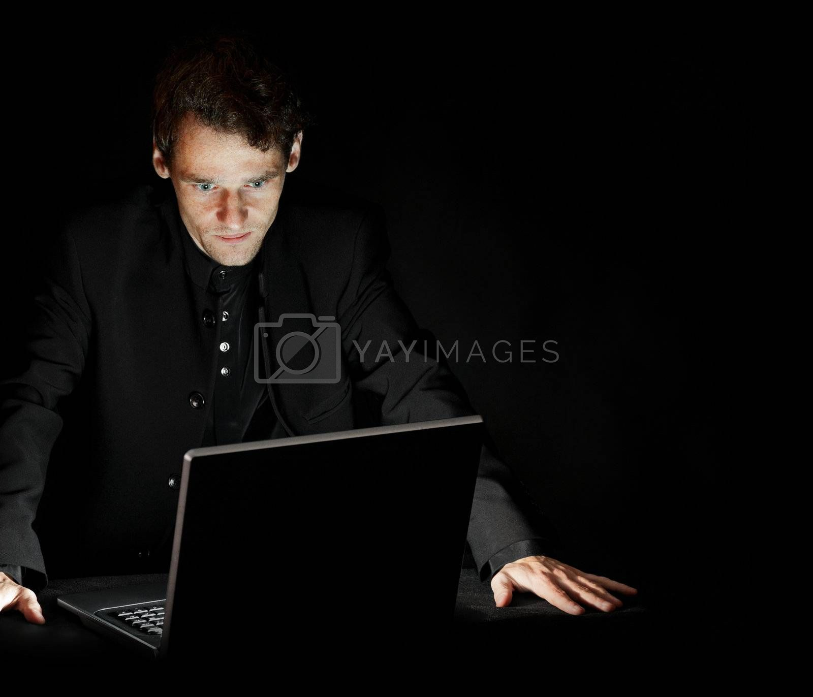 Portrait of hacker with laptop on dark background