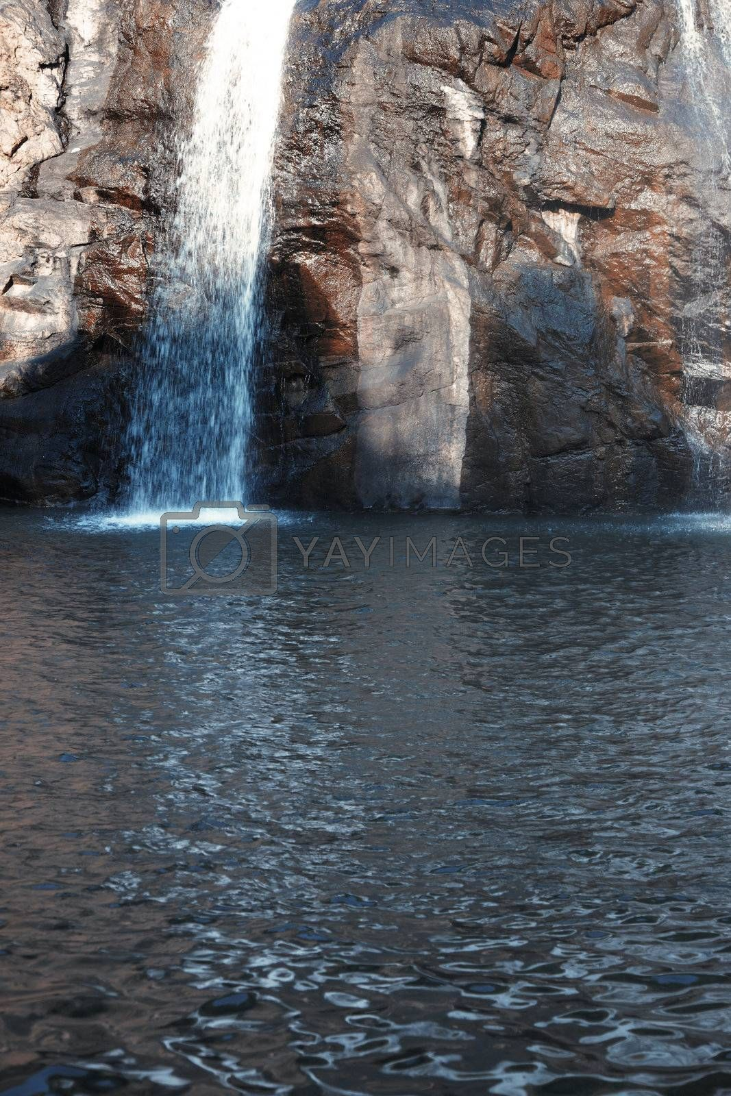 Waterfall in the rock. Vertical photo