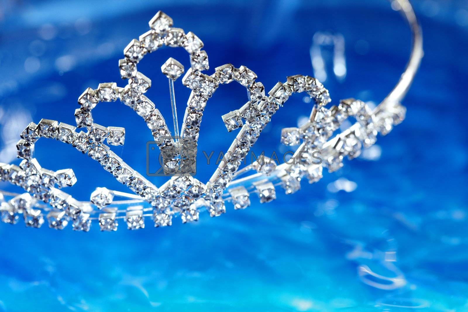 Close-up photo of the silver diadem with diamonds on a blue water background. Shallow depth of field added by macro lens for natural view