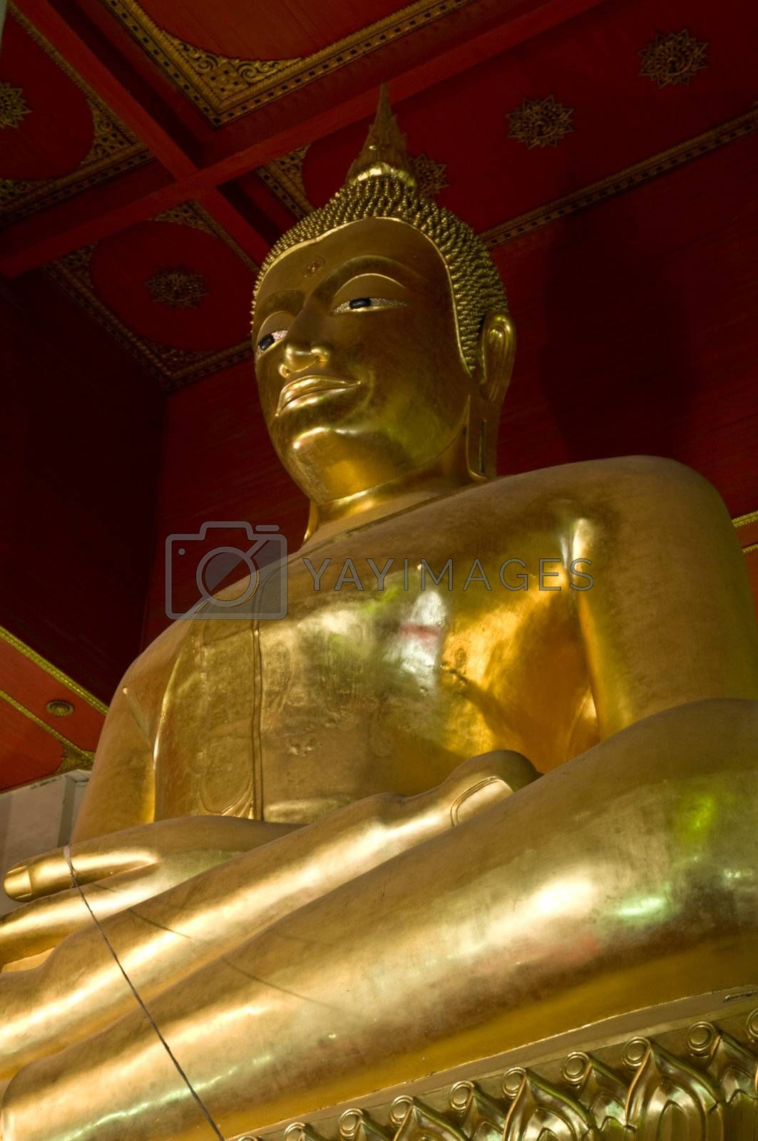 Red roofed hall with ornaments and a tall golden Buddha statue. Ayutthaya city is the capital of Ayutthaya province in Thailand. Its historical park is a UNESCO world heritage.
