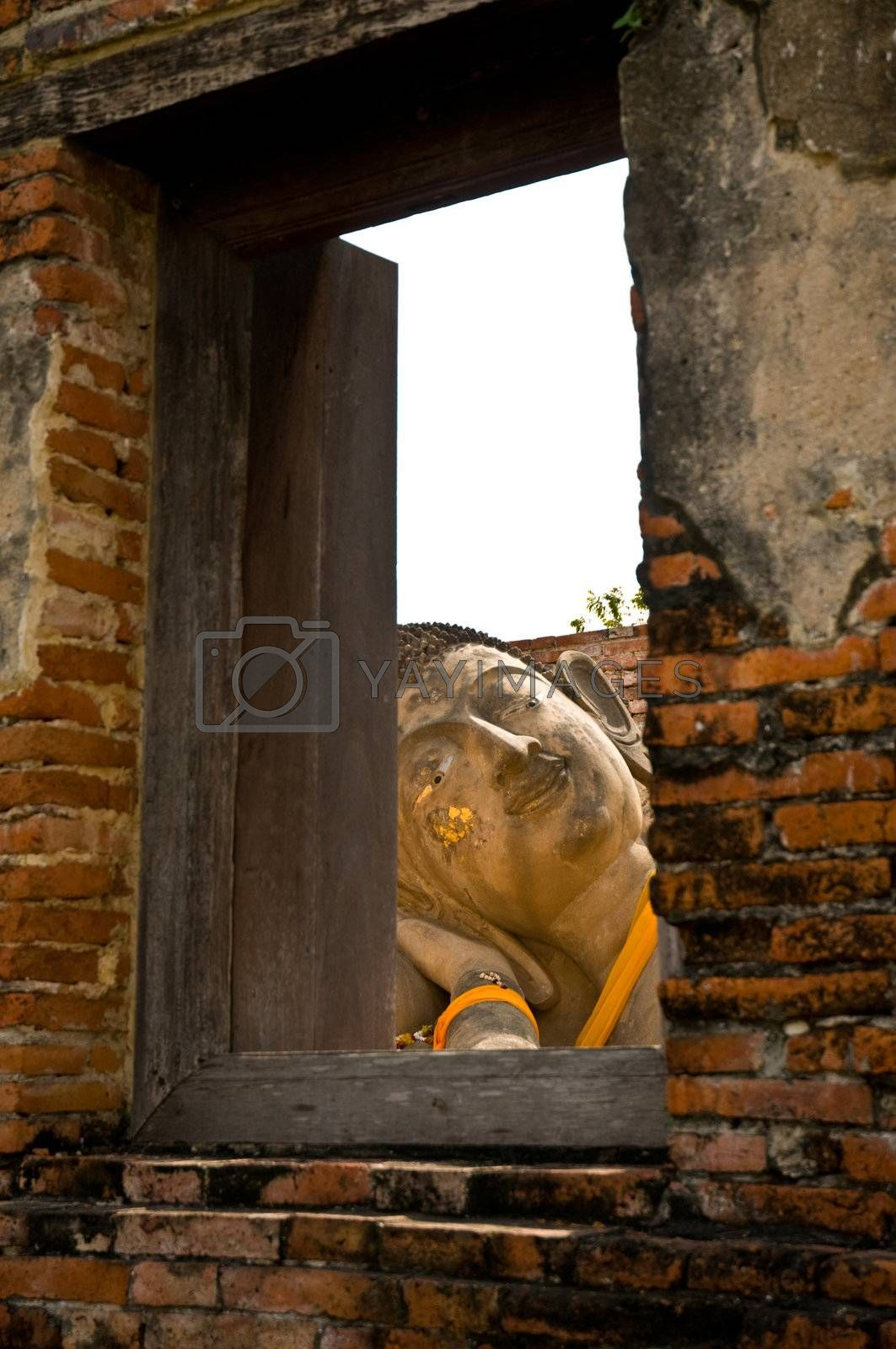 Reclining Buddha, view through a window with a wooden frame. Ayutthaya city is the capital of Ayutthaya province in Thailand. Its historical park is a UNESCO world heritage.