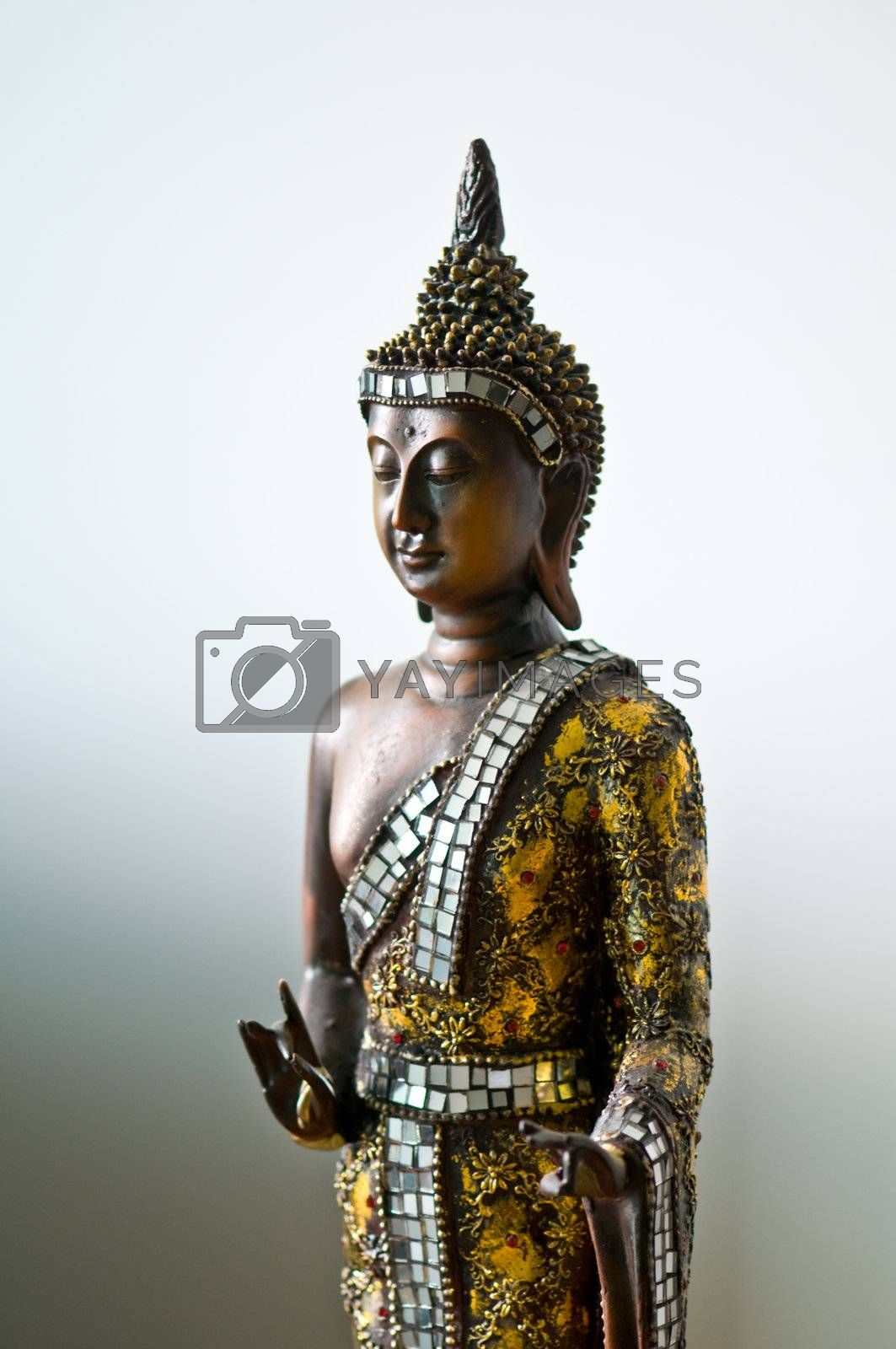 Buddha statue with a golden robe with a white grey background