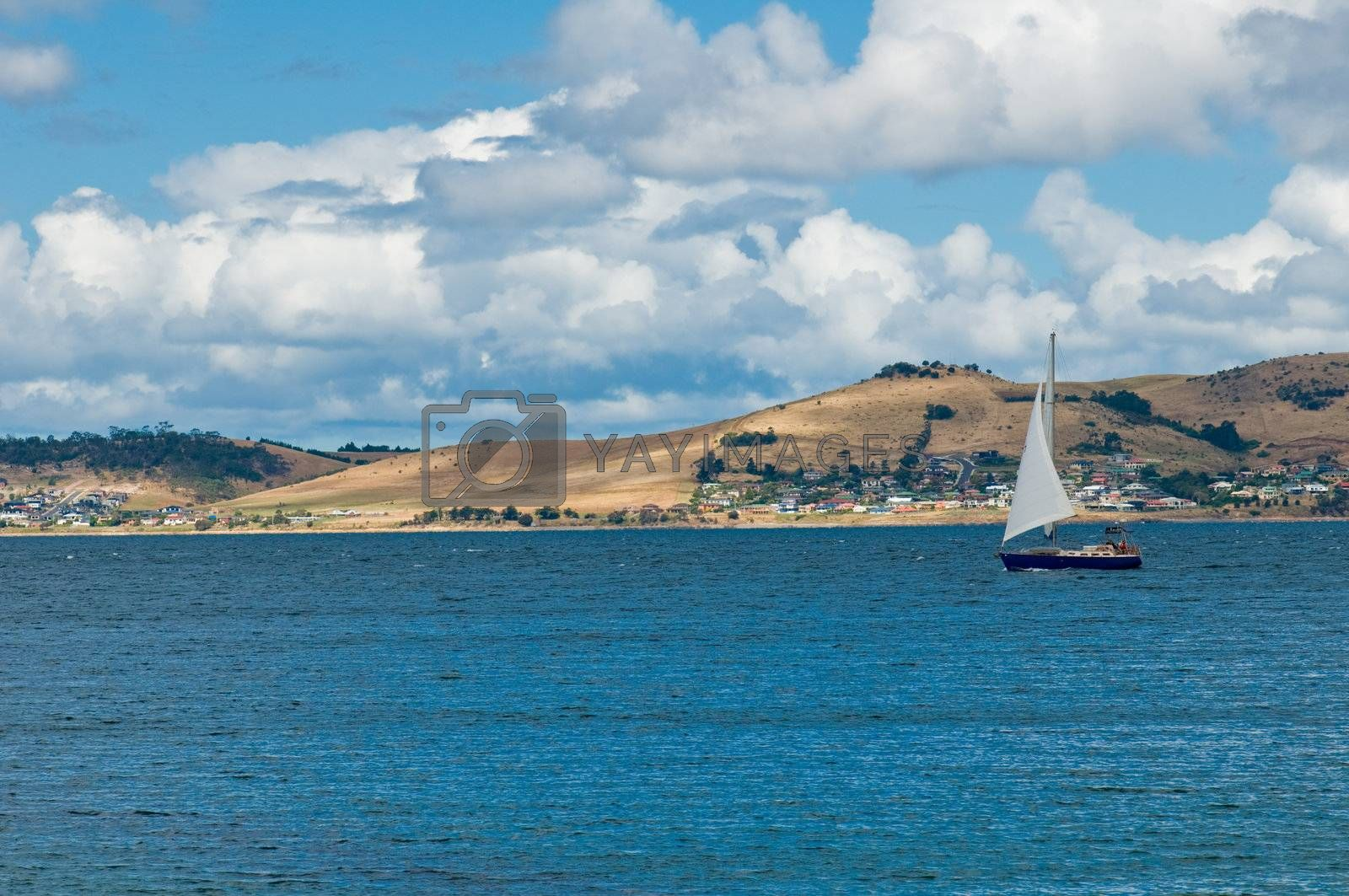Luxury yacht sails in blue waters towards a harbour along the coast line. The sky is summer blue with nice big summer clouds.