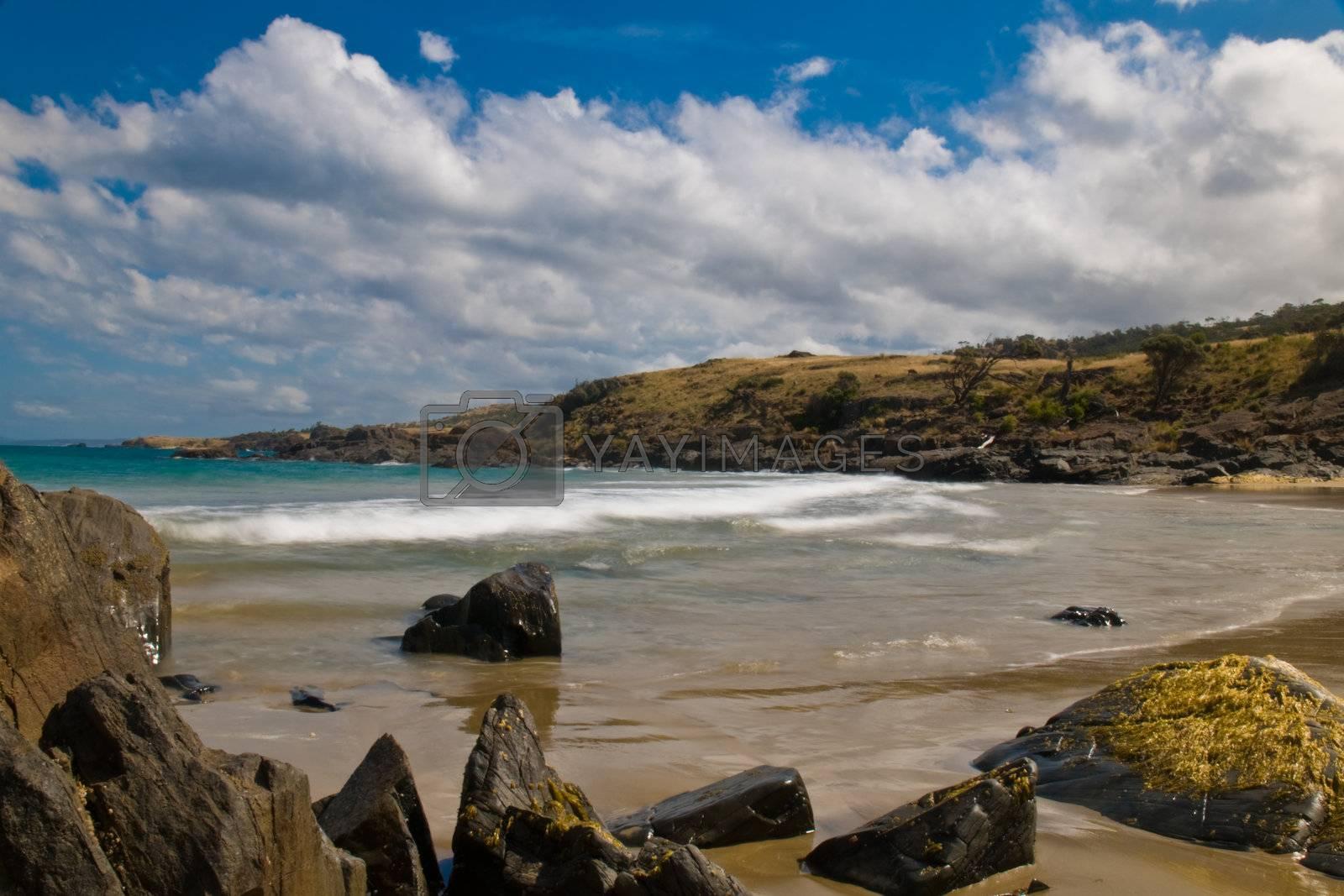 Sea landscape with bay, rock, beach, coastline, blue sky, long exposure, incoming waves