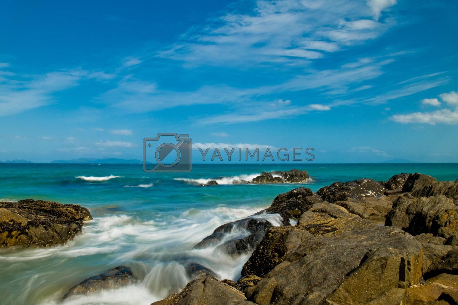 Sea landscape with rock beach coastline, blue sky, long exposure, incoming waves