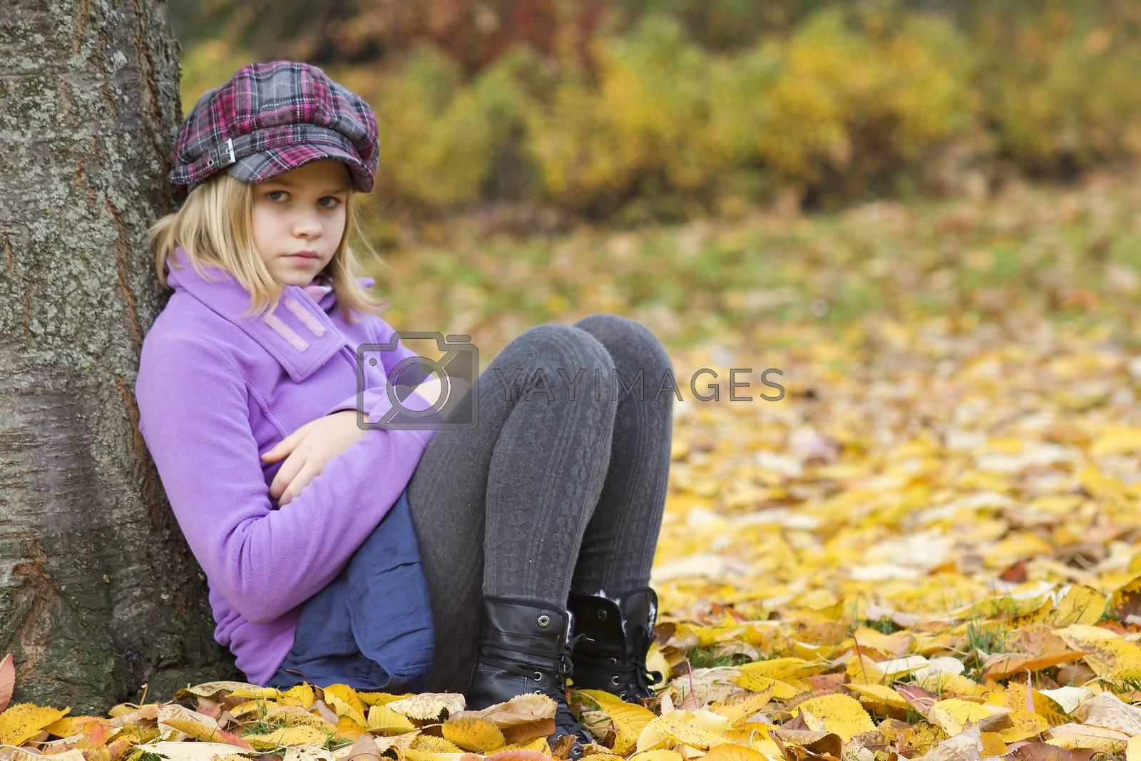 Full length portrait of a little girl sitting under tree in autumn park