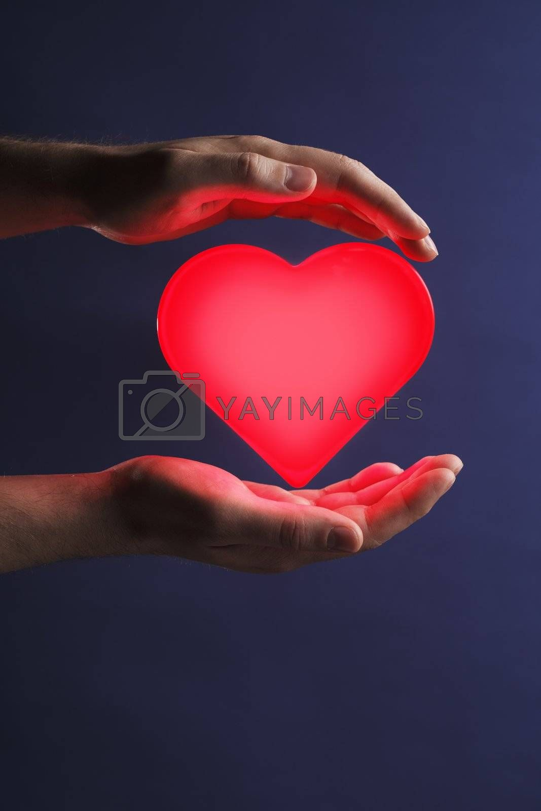 Man holding a glowing red heart in his hands