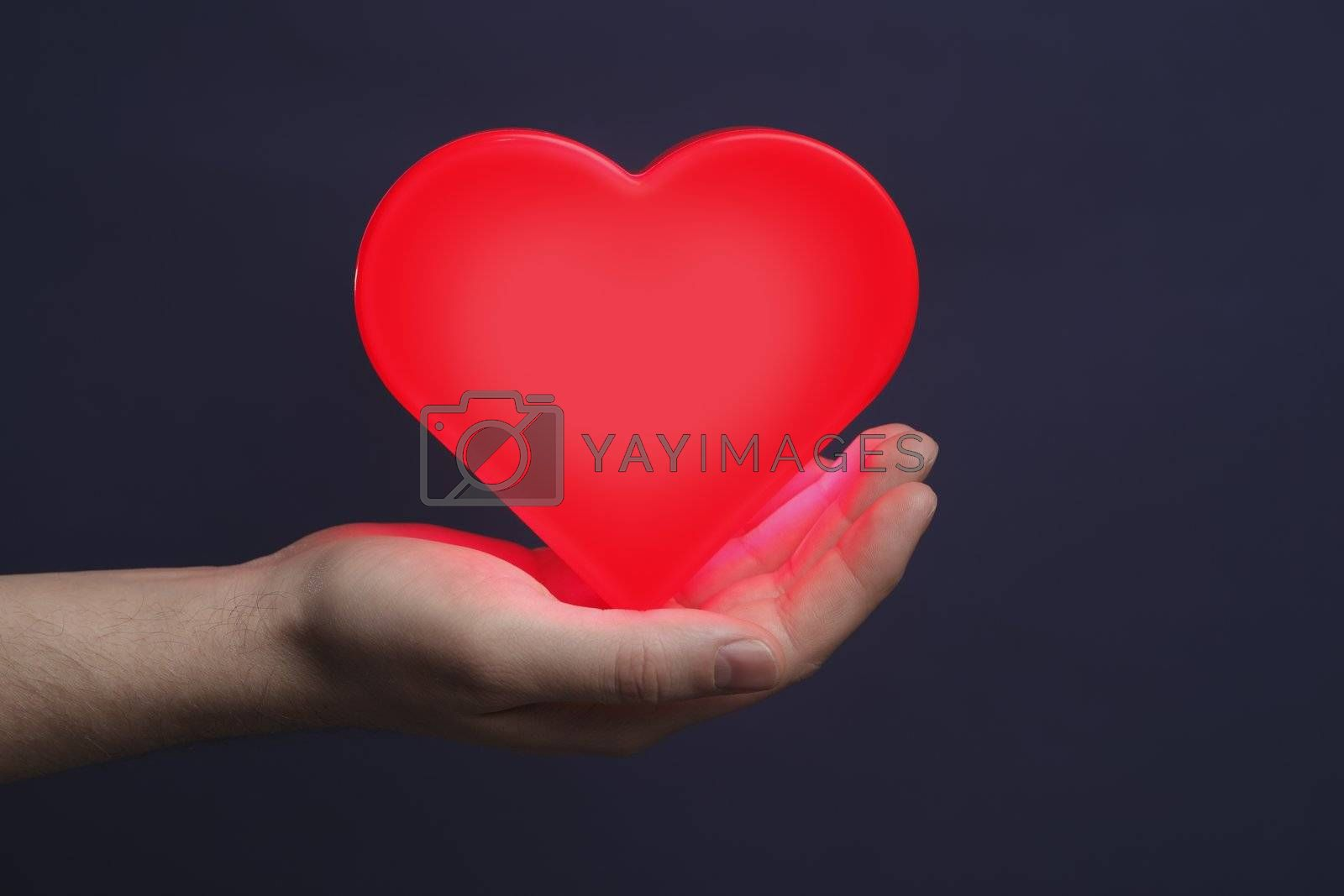 Man holding a red glowing heart on his palm.