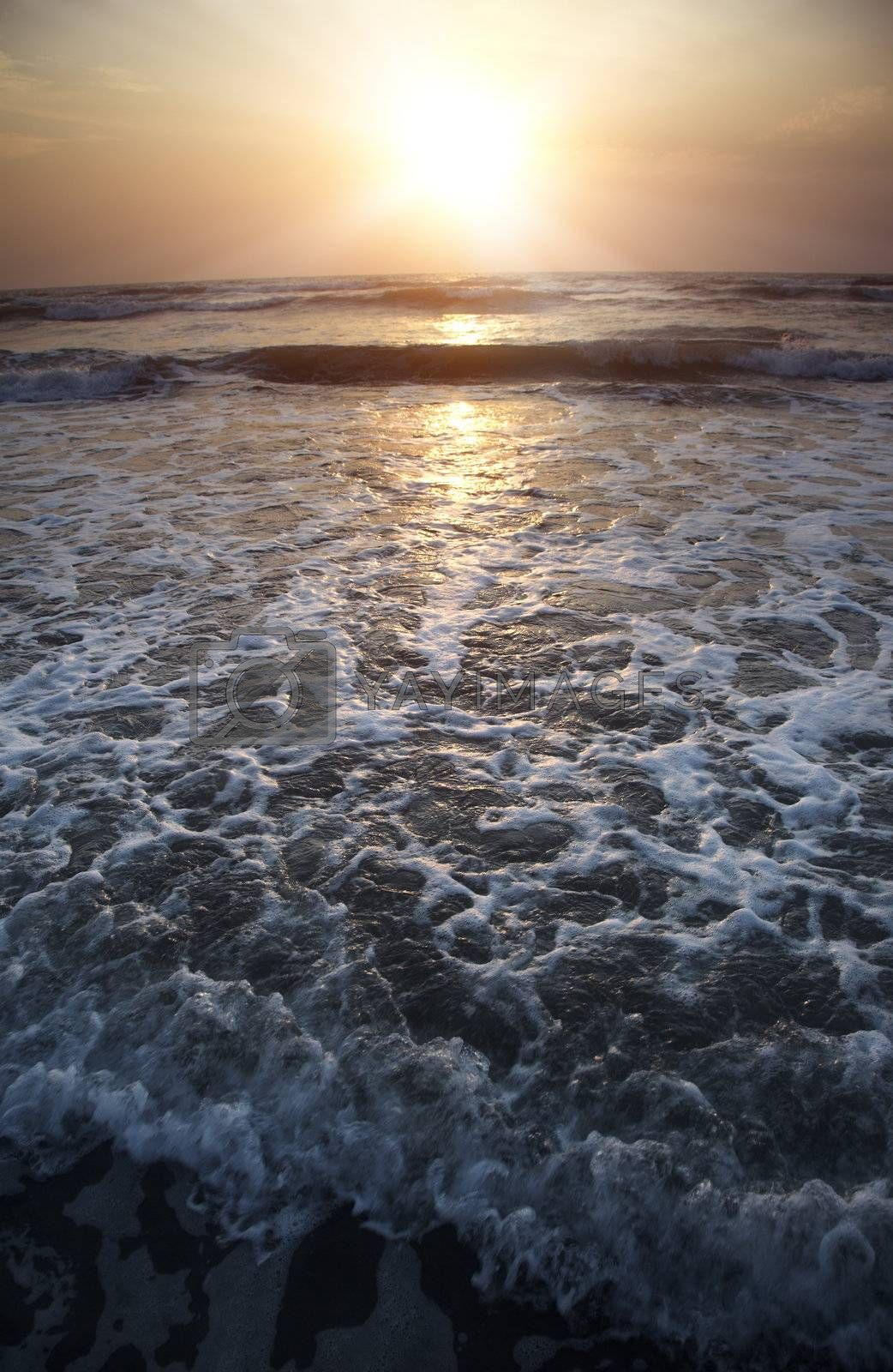 Seascape vertical photo of the ocean during twilight and sunset. Dark colors for the dramatic effect