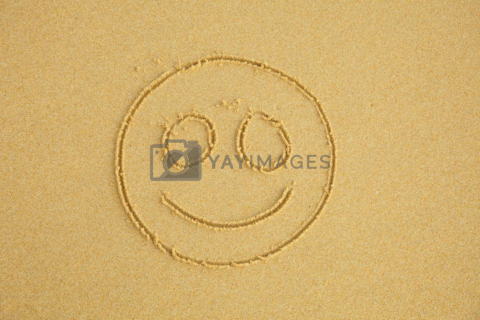 Smiling face drawn on beach sand