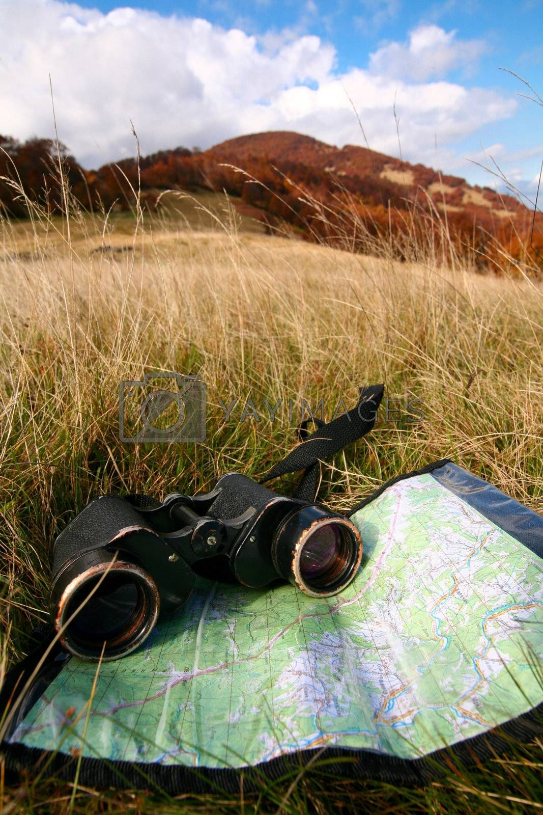 An image of binoculars and map on grass
