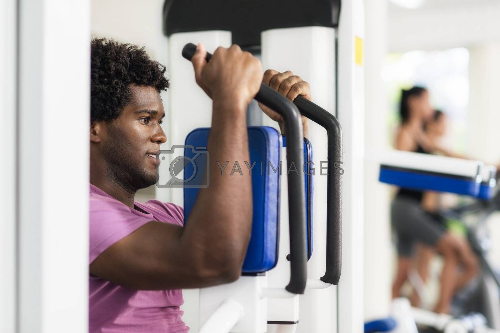 Young african american man training in fitness gym by diego_cervo
