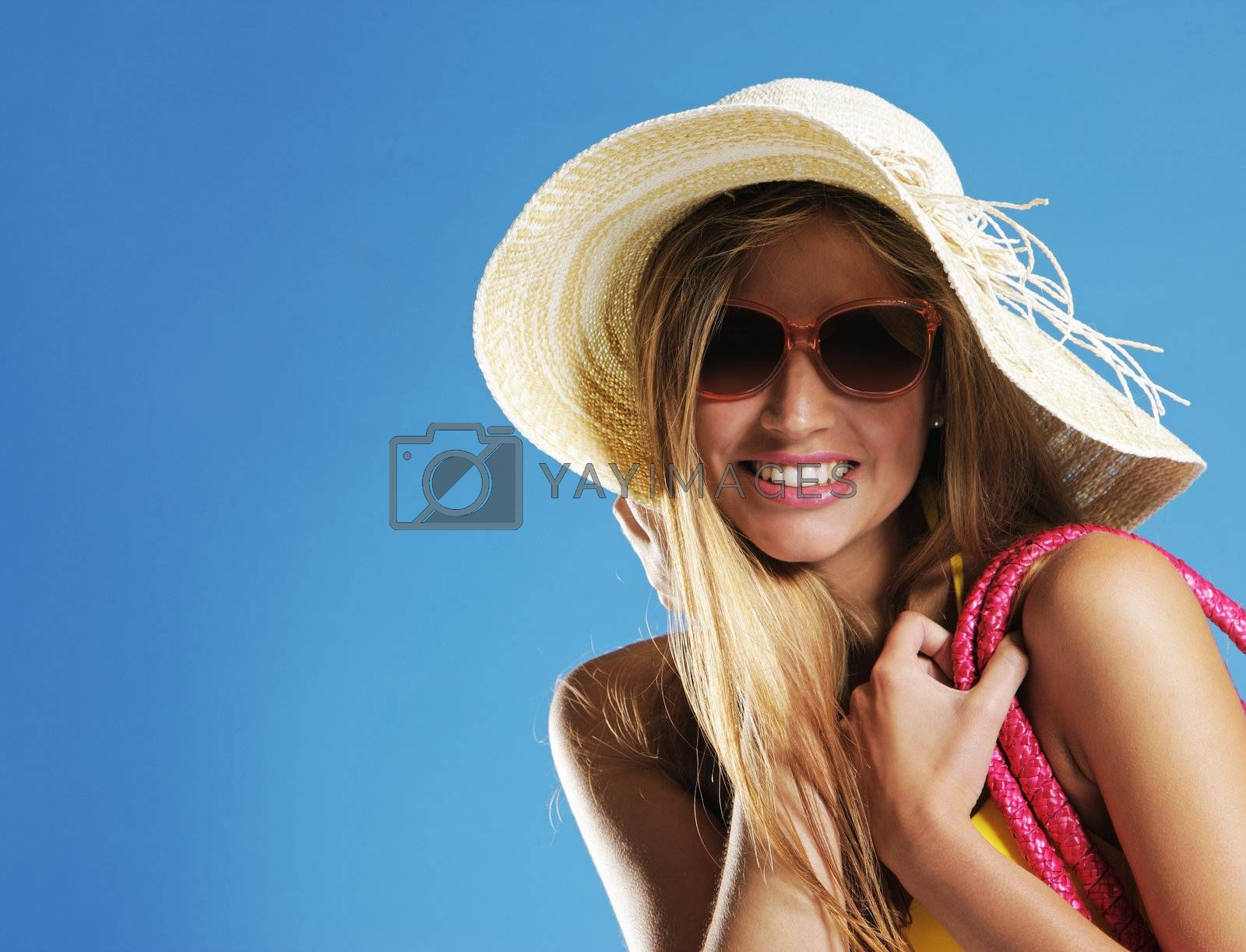 Smiling young woman against blue background, copy space