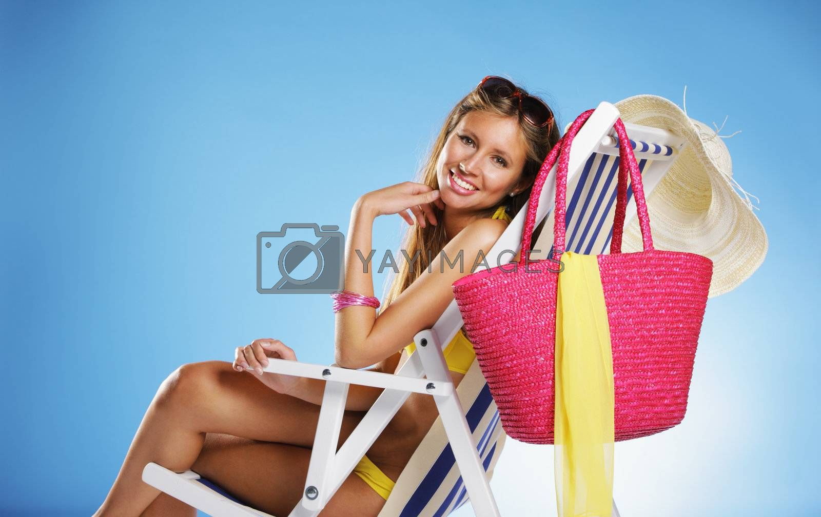 Beautiful young woman relaxing on beach chair