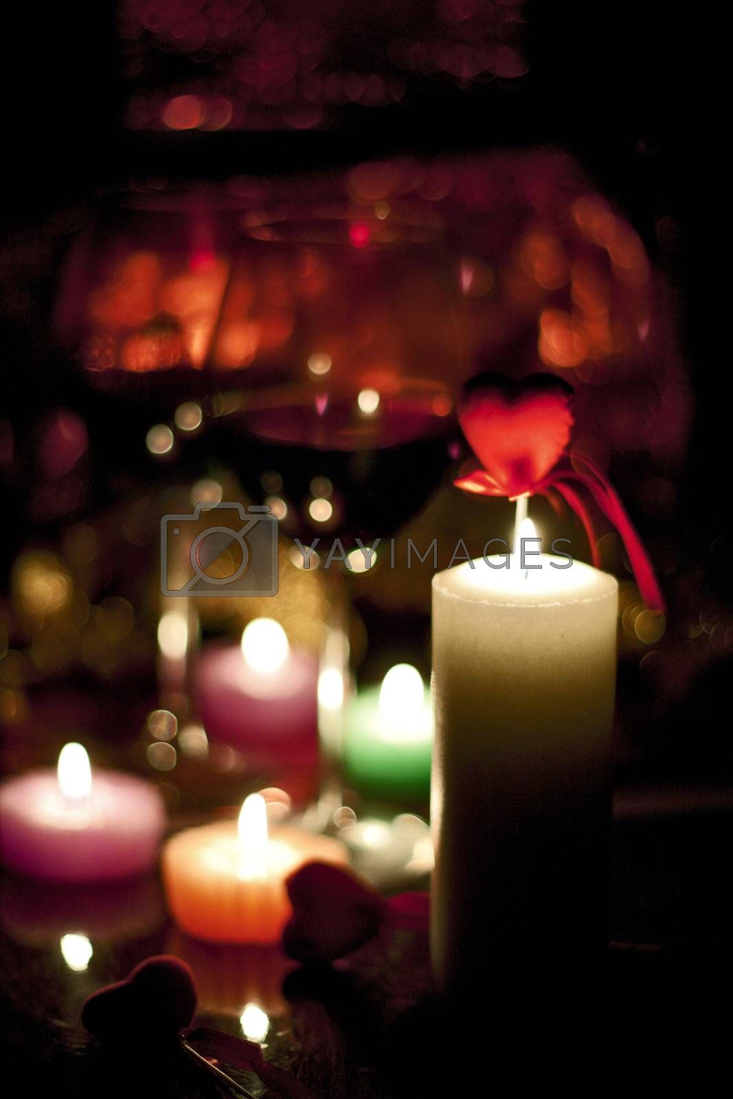 romantically colored candles burning with a beautiful reddish bokeh