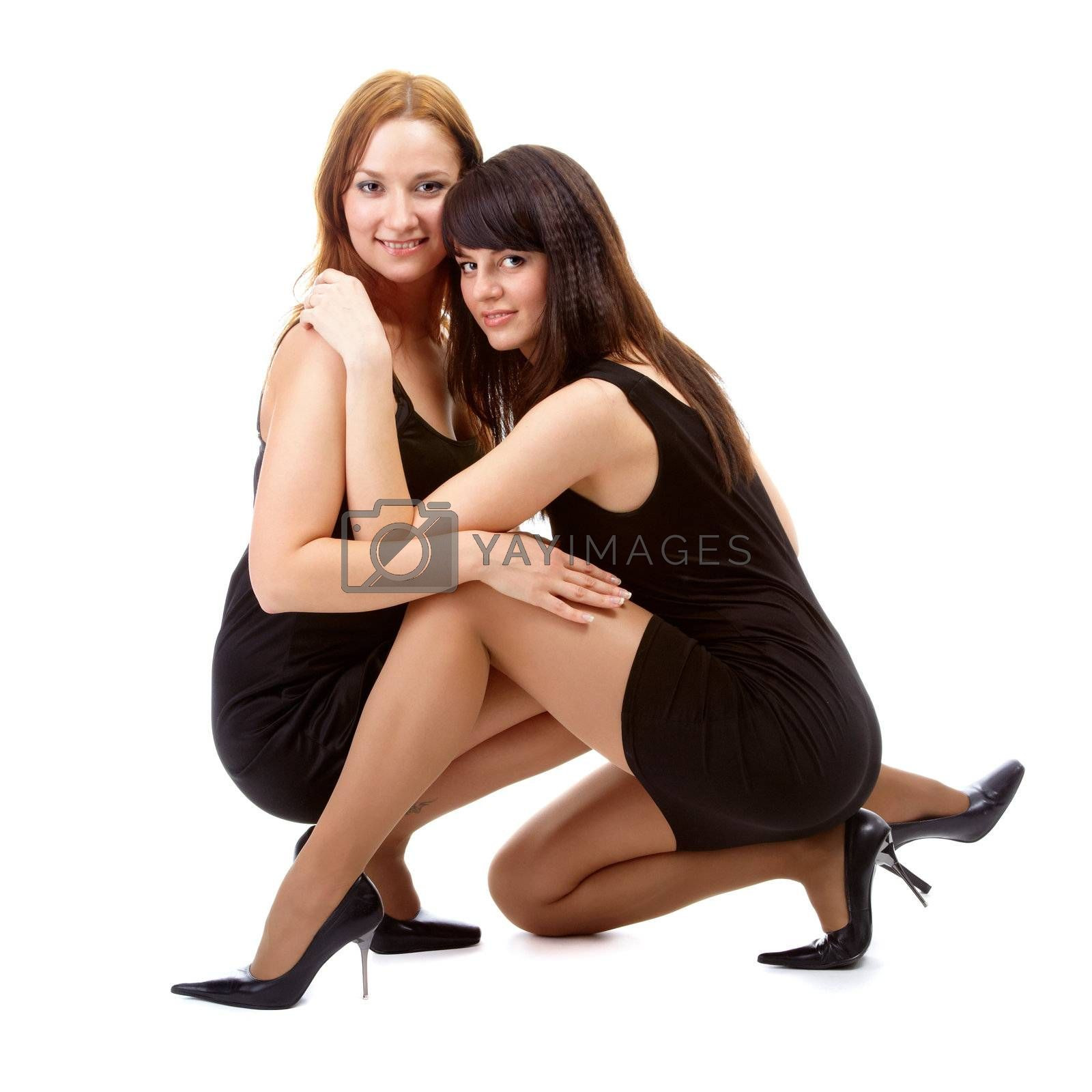 portrait of two beautiful models posing in black dresses