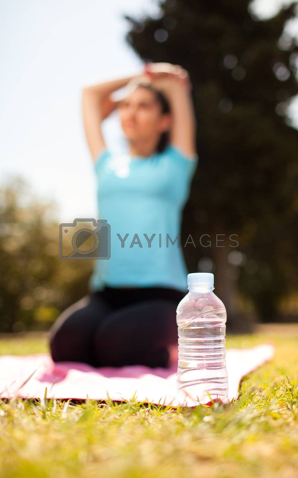 hydration concept bottle of water with woman stretching on background