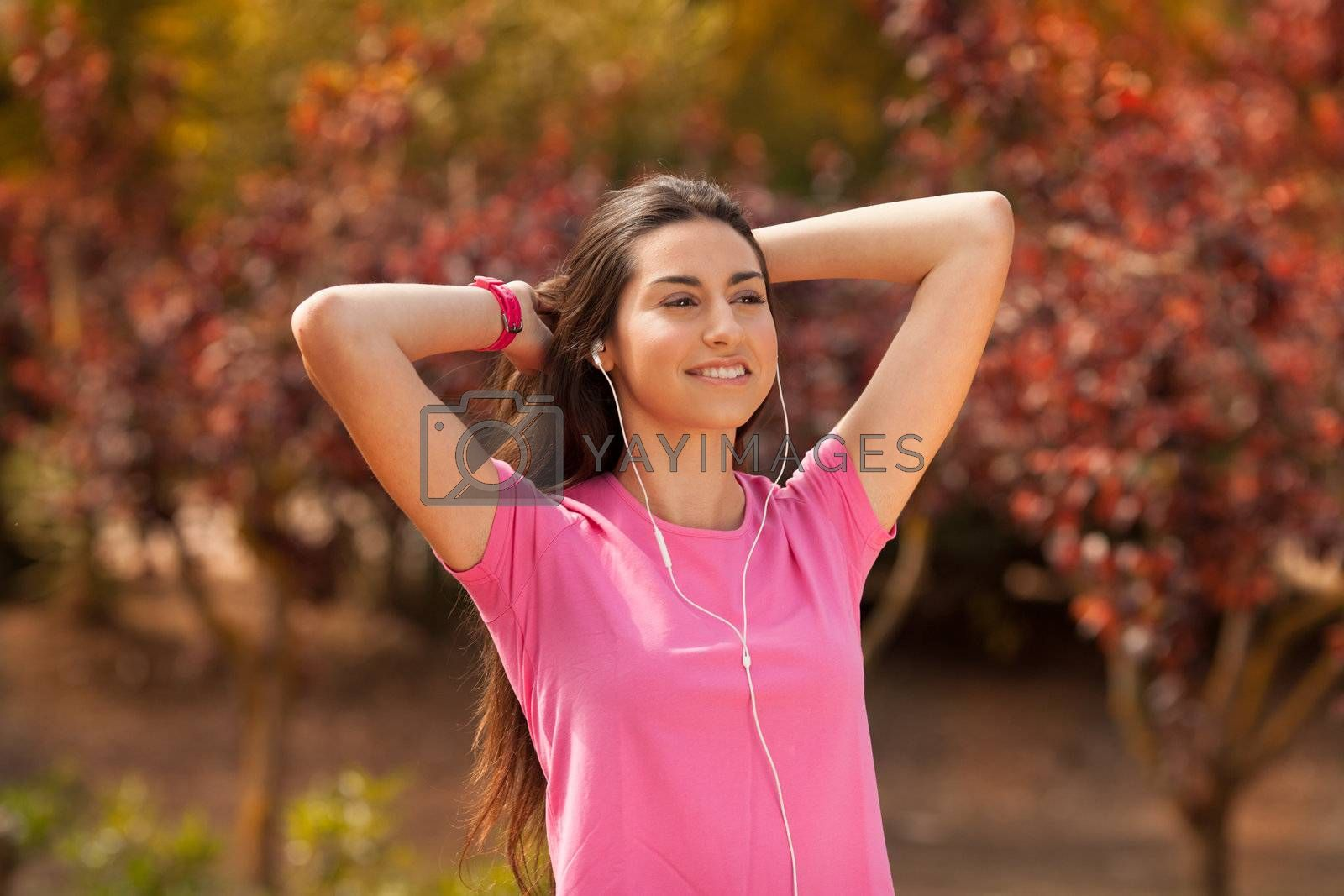 Young beautiful woman with sporty look enjoying with headphones outdoors
