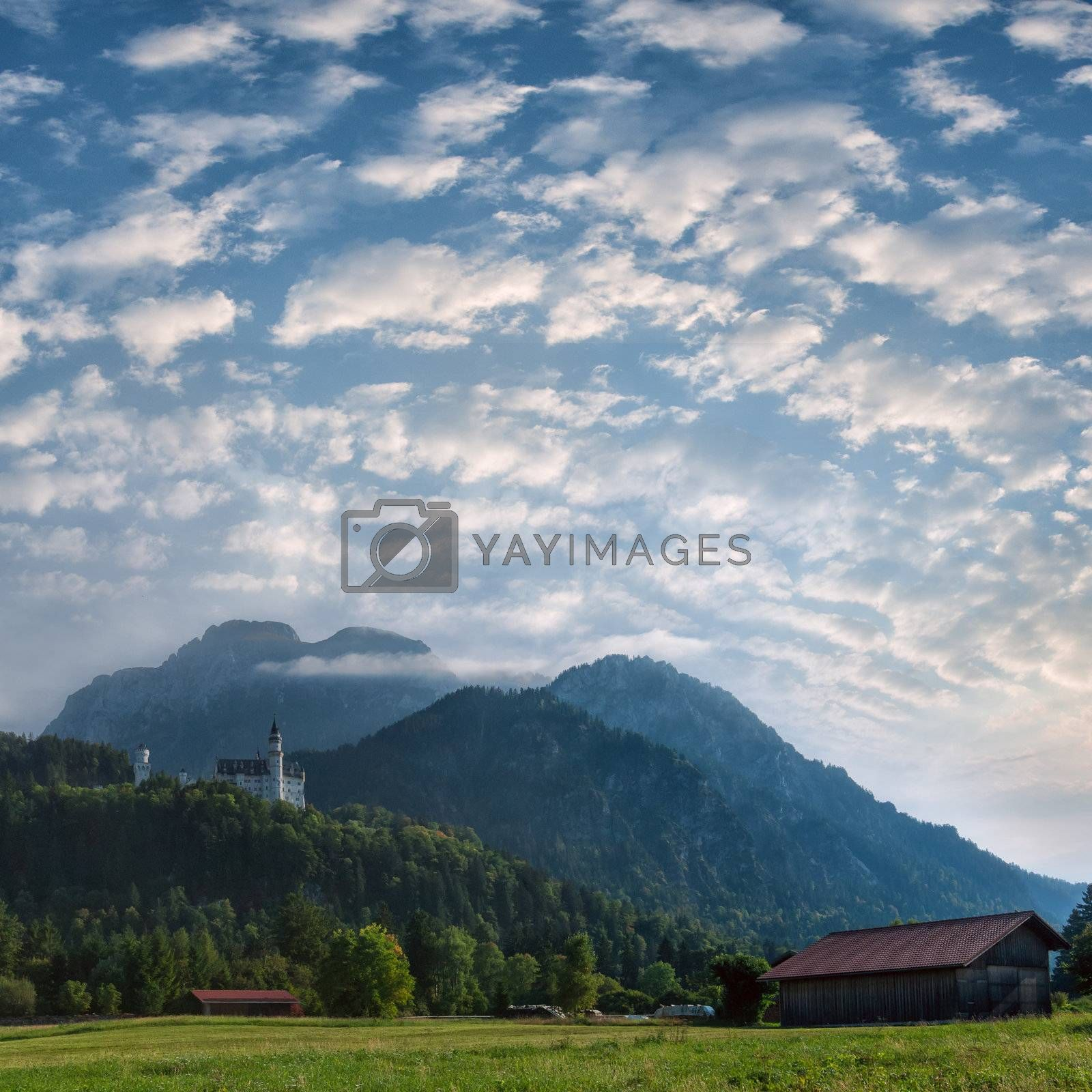 Mountain landscape with castle on the top and beautiful sky on background