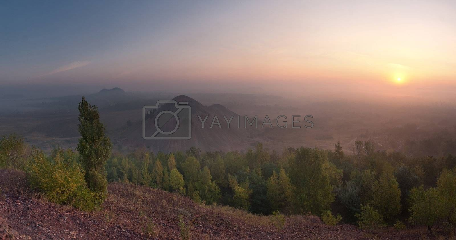 The top view landscape on valley with waste heaps in fog and rising sun