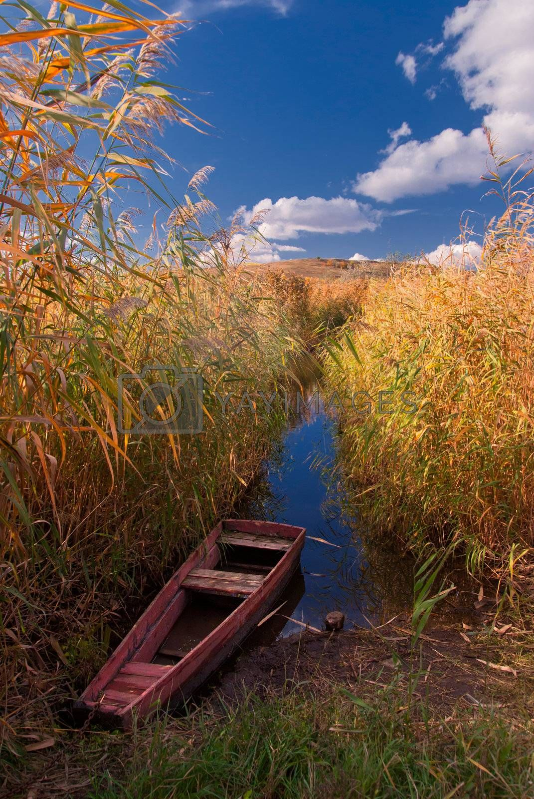 The lonely boat on the river, autumn landscape
