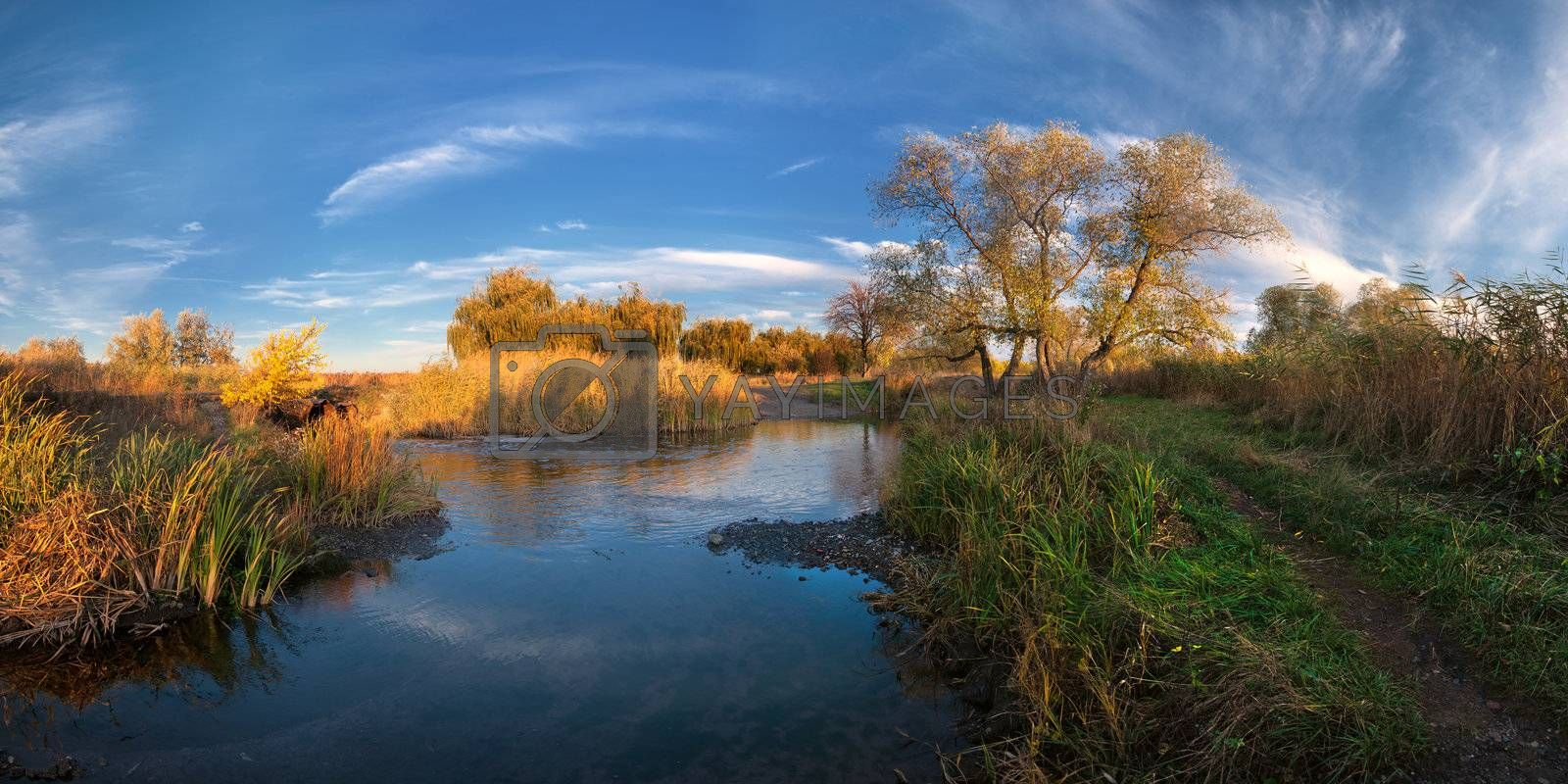 Colorful autumn landscape on evening river with beautiful clouds in the sky. Panorama