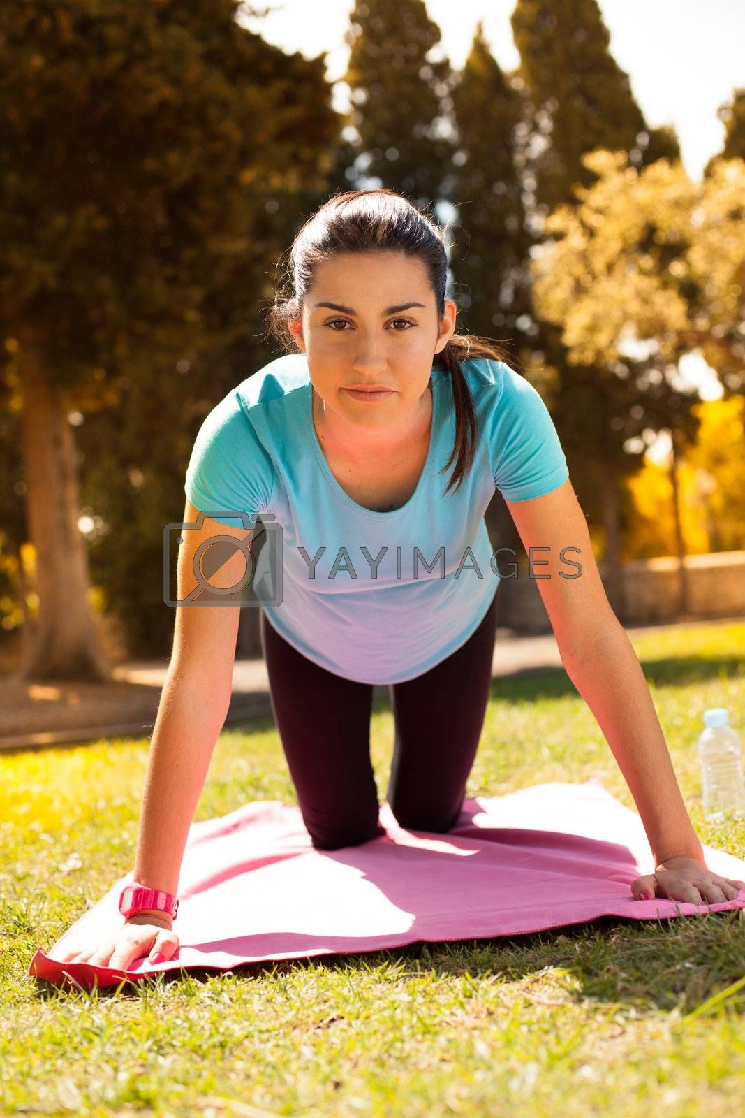 young beautiful woman work out arms on a park