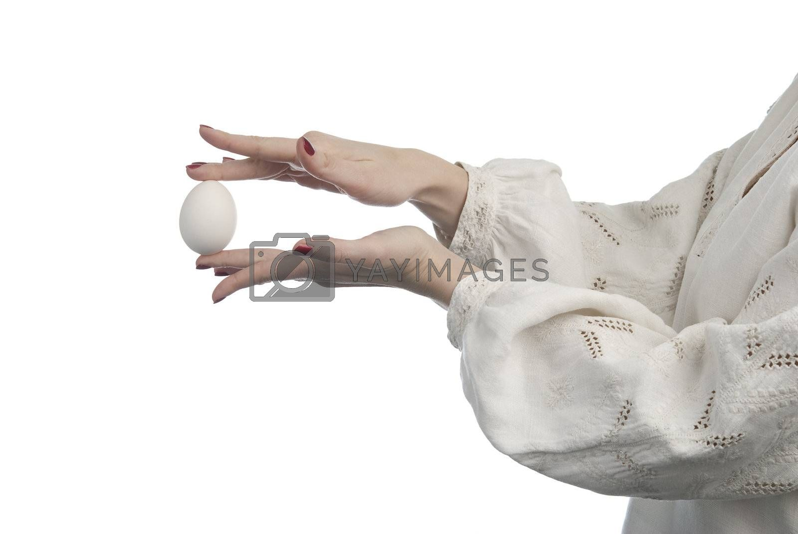 Woman's hands holding the egg. Traditional Ukrainian dress. Isolated on white