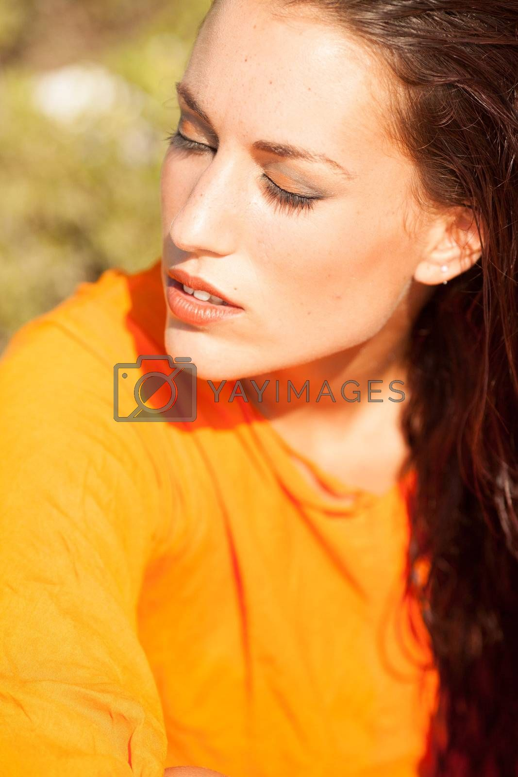 Portrait of young beautiful model posing on outdoors with orange shirt