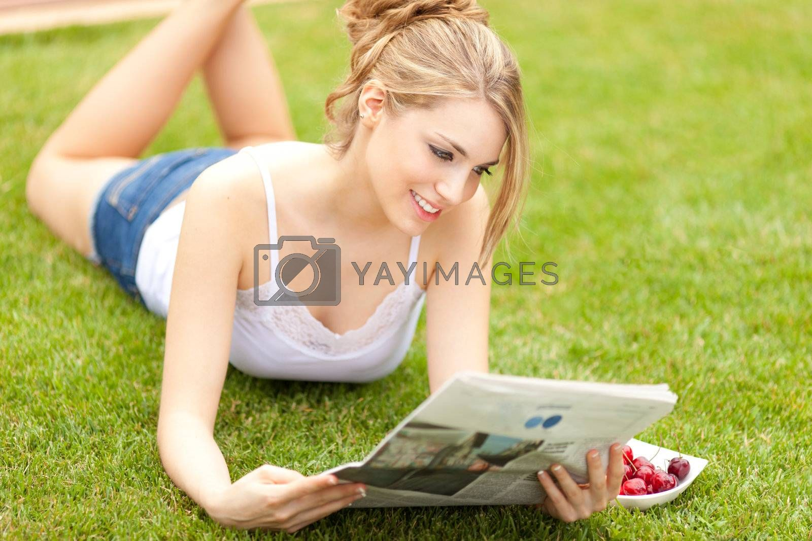 young beautiful blonde girl reading the newspaper and eating cherries on the grass