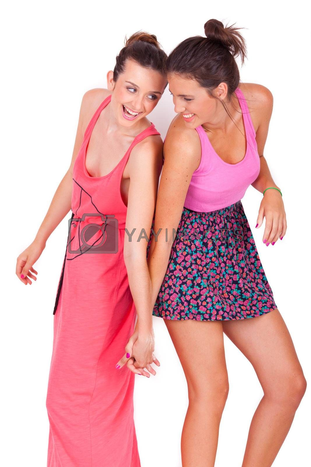 portrait of two young beautiful friends playing and having fun on white background