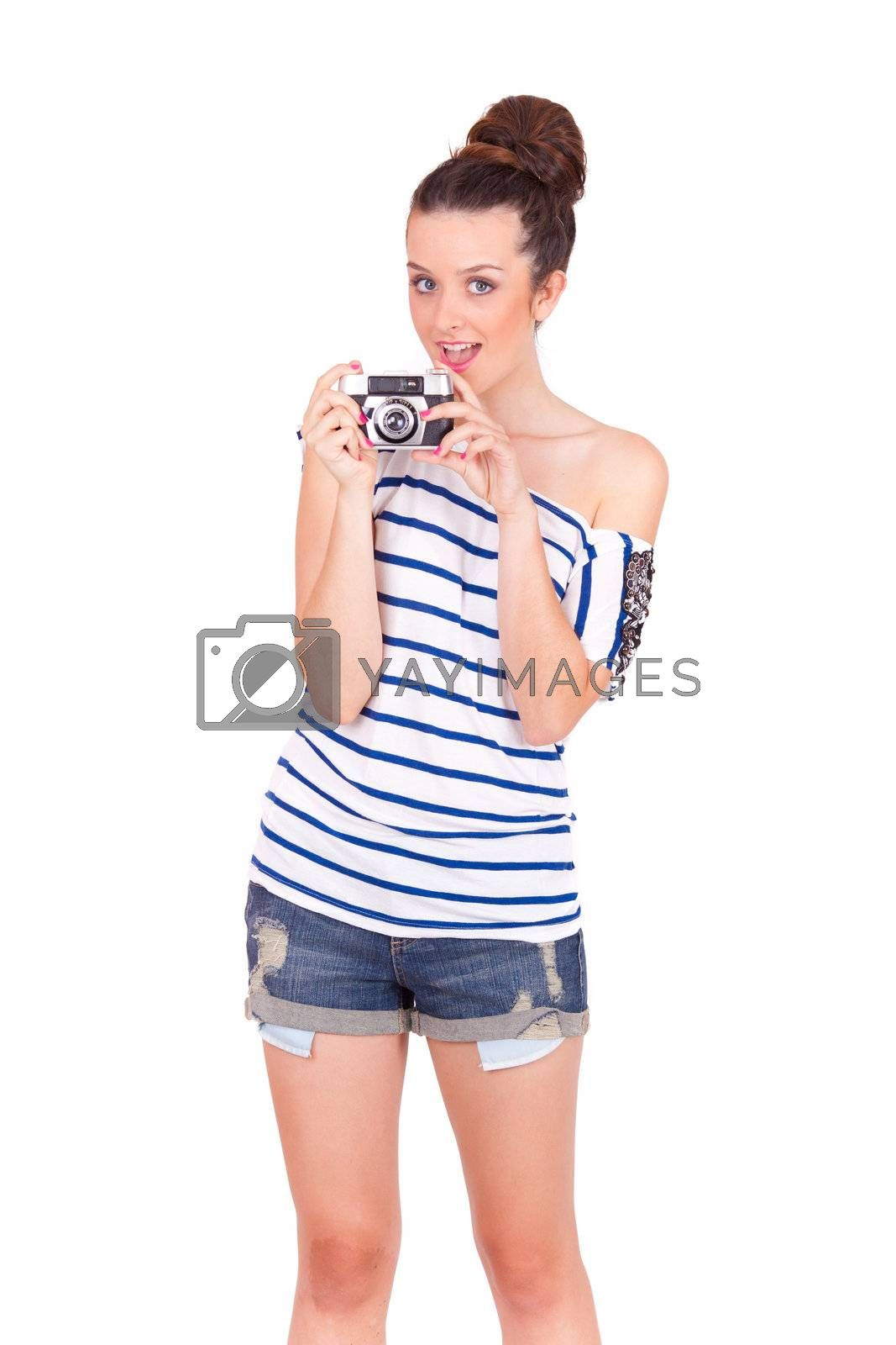 isolated portrait of a young women playing with a vintage camera on white background