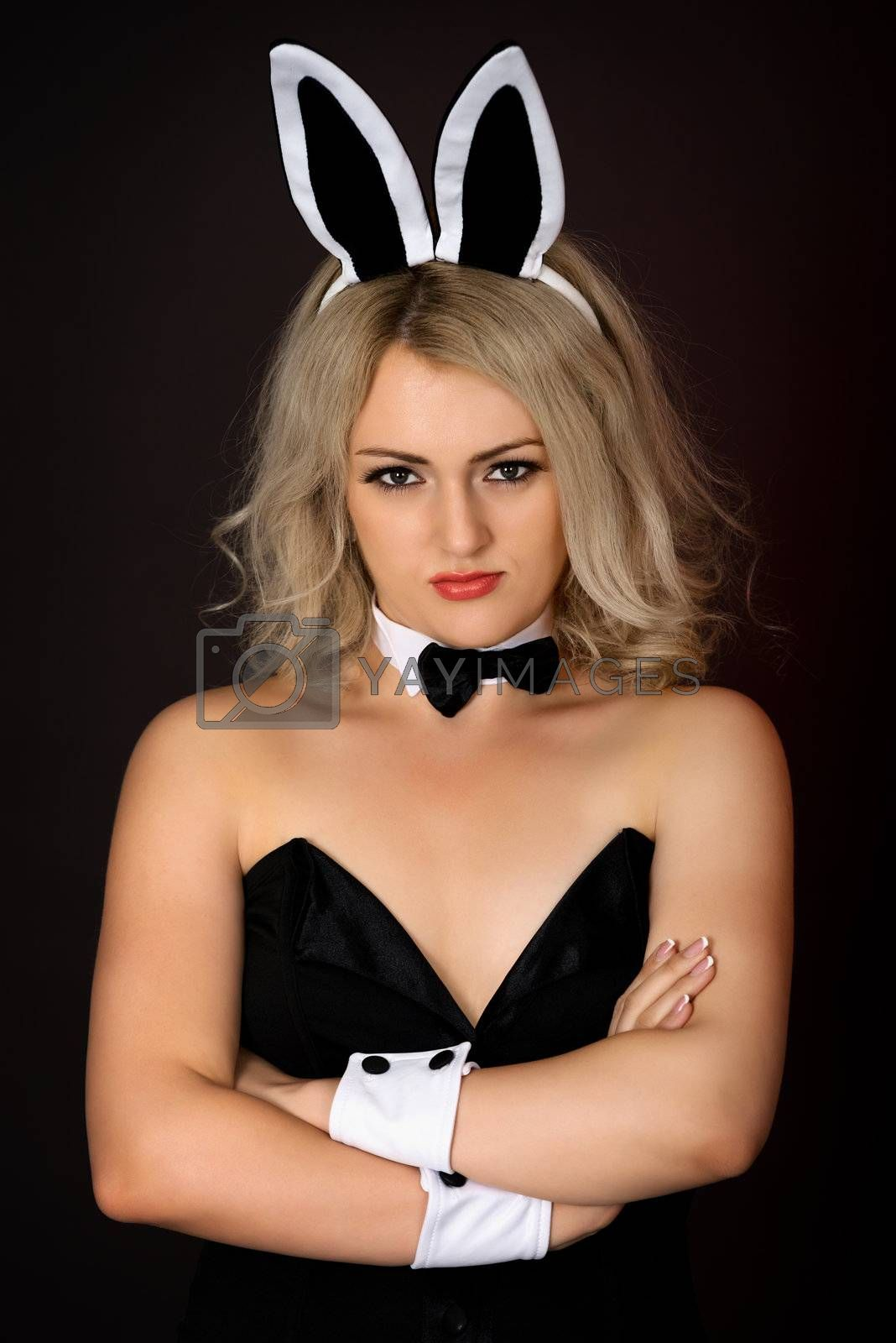 A sullen girl in sexy bunny costume against a dark background