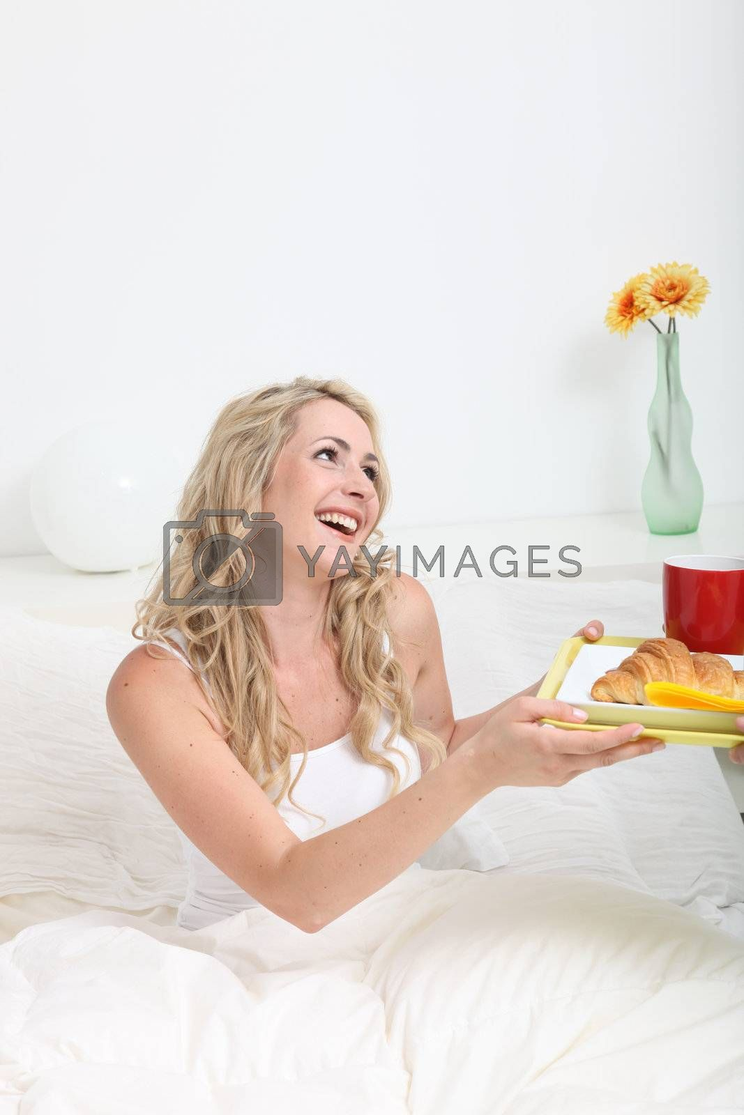 Woman smiling graciously as she receives breakfast in bed in celebration of a special event